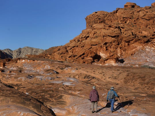 In this January file photo, visitors hike at Gold Butte National Monument in Gold Butte, Nev.