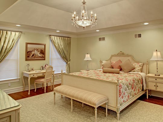 The crystal chandelier in the trey ceiling creates a focal point. Bedside lamps and recessed lighting illuminate the room.