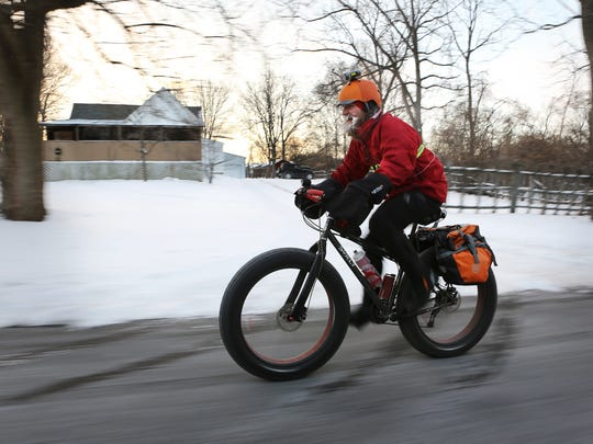 In a Feb.19, 2014 photo, Fraser Cunningham, 56, of Madeira, Ohio, a GE Engineer, bicycles home from work in single digit temperatures.