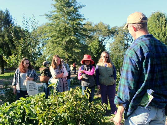 Backyard Abundance director Fred Meyer, right, offered information about edible landscapes Saturday to attendees of an Edible Forest Walkabout event at Wetherby Park.