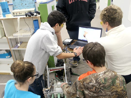 From left to right: City High ninth-graders Mairead Moore, Victor Kalil and Nick Schintler work with their advisor Vicky Pedersen during a FIRST Tech Challenge robotics meeting.