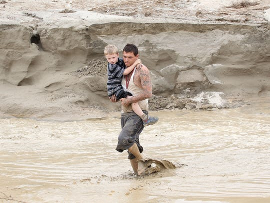 Mike Garcia, left, carries William Rohr across flood waters to his family after rain made Varner Road impassable on Sept. 8, 2014.