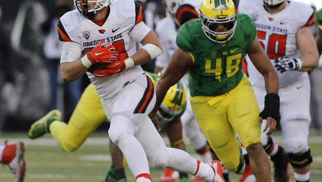 Oregon State running back Ryan Nall pulls away from Oregon's Rodney Hardrick on a touchdown run during the second half of an NCAA college football game in Eugene Ore., on Friday, Nov. 27, 2015. Oregon won 52-42. (AP Photo/Timothy J. Gonzalez)