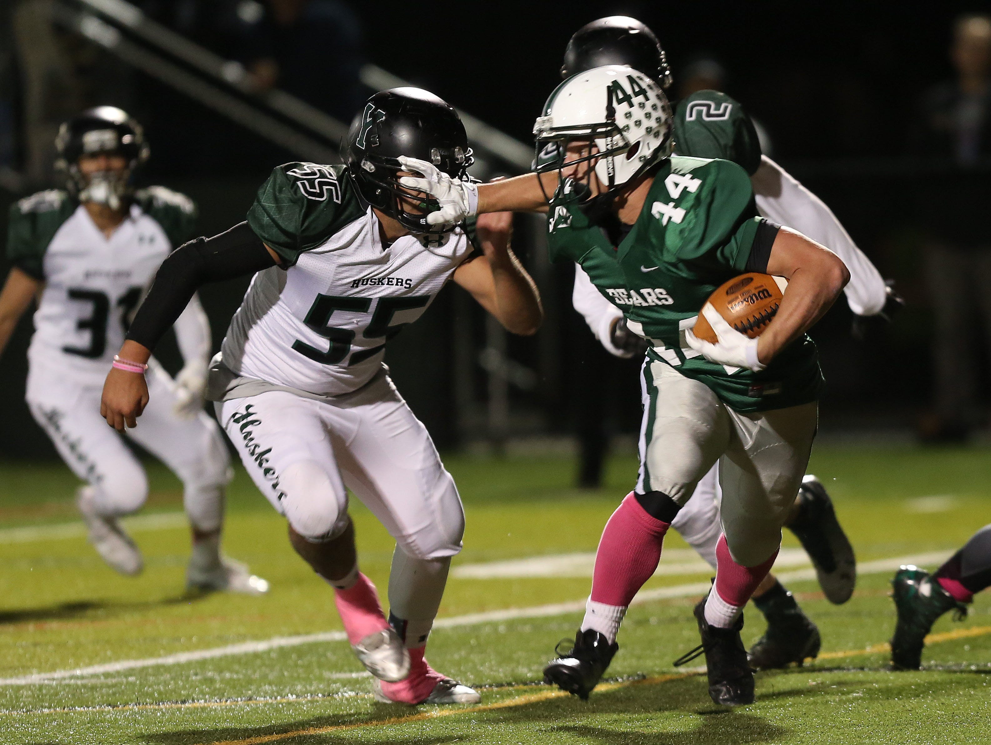 Yorktown's Justin Cavallo (55) and Jesse Bambach (2) stop Brewster's Jack Guida (44) on a first half run during a football playoff game at Brewster High School Oct. 23, 2015.