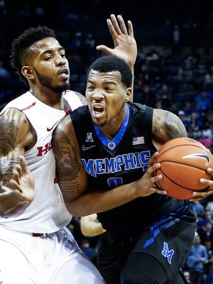 University of Memphis forward K.J. Lawson (right) drives for a layup against University of Houston defender Devin Davis (left) during first half action at the FedExForum.