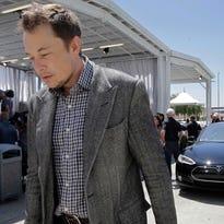 In a 2012 file photo, Tesla CEO Elon Musk walks past the Tesla Model S