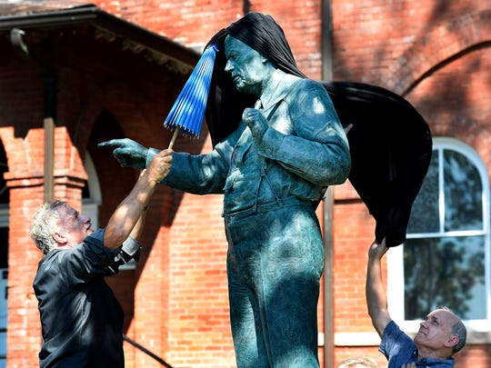 Actor John de Lancie, left, and musician Dan Barker remove the drape off the Clarence Darrow statue during the dedication ceremony in front of the Rhea County Courthouse, Friday, July 14, 2017, in Dayton, Tenn.