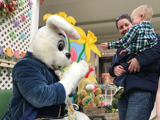 Amy Jett, of Rosendale, smiles moments after her 2-year-old son, Wesley, high-fives the Easter bunny.