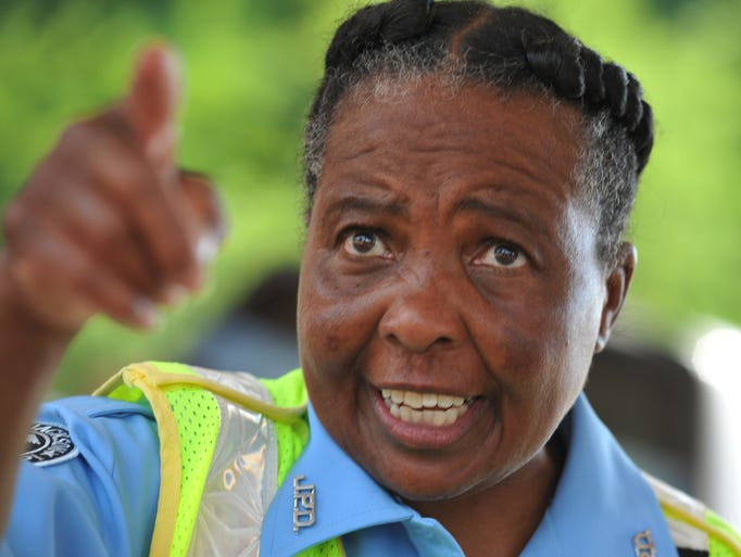 Crossing guard Charlotte Williams points as she works