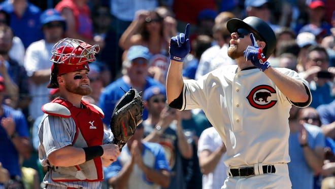 Chicago Cubs second baseman Ben Zobrist celebrates his home run as Cincinnati Reds catcher Tucker Barnhart  looks on during a game at Wrigley Field.