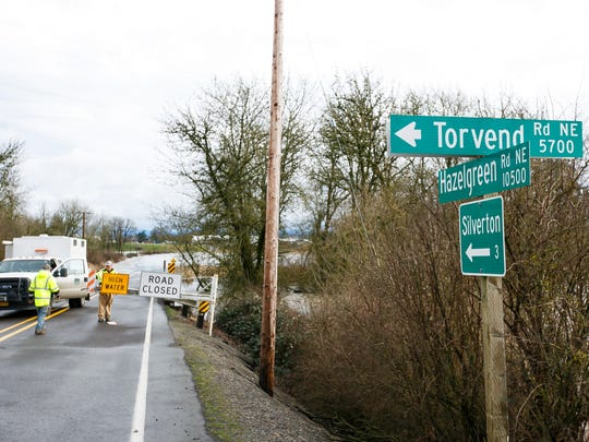 Marion County Public Works attaches a reflector to a road closure sign along Hazelgreen Road NE near Torvend Road, just west of Silverton, on Thursday, Feb. 9, 2017. Water from Rudding River spilled over the road, and crews except the level will reach its peak on Friday.