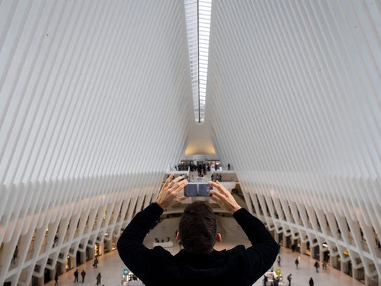 A man takes a photo inside the Oculus at the World