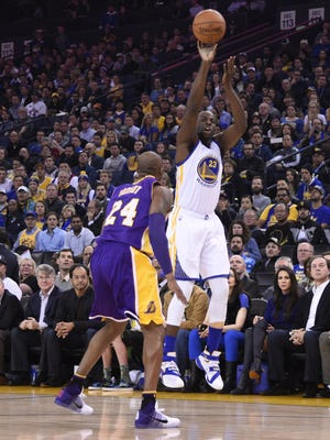 Golden State and former MSU forward Draymond Green (23) shoots over Los Angeles Lakers star Kobe Bryant (24) on Thursday in Oakland, Calif.