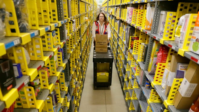 Amazon employee Dena McQueen maneuvers a cart with items collected in an aisle filled with items in the online retailer's Prime Now fulfillment center on Milwaukee's south side.
