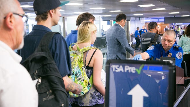 Passengers have their boarding passes and IDs checked at the TSA PreCheck line at Gate A in Terminal 4 at Phoenix Sky Harbor International Airport in Phoenix on Thursday, July 24, 2014.