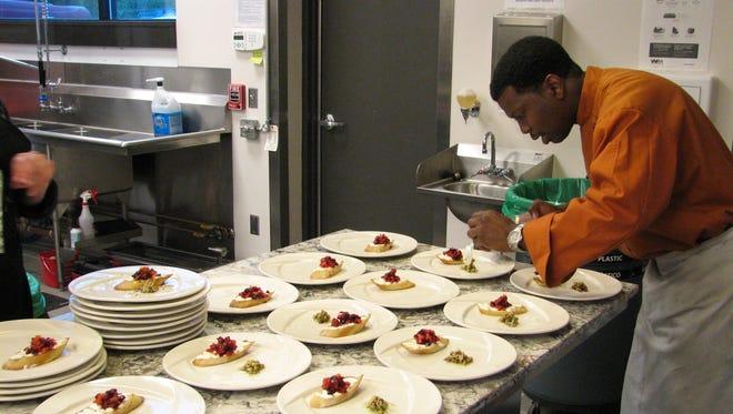 Chef Carlos Davis of Riffs Catering works at Mesa Komal inside the Casa Azafran community center.