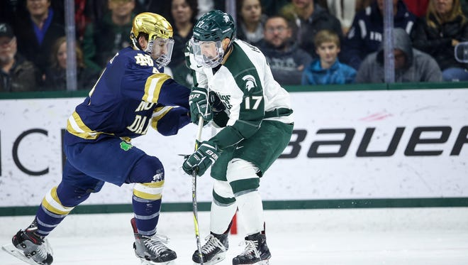 Michigan State sophomore forward Taro Hirose is checked by a Notre Dame player during Saturday's game.