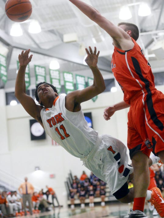 William Penn's Jacquez Casiano, left, takes a diving shot against Central York's Jared Wagner during Friday night's YAIAA boys' basketball championship game at York College. William Penn won, 58-45.
