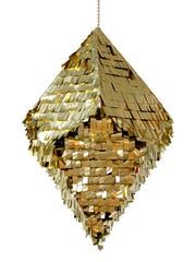 A gold crystal pinata. Modern pinatas can be sleek and geometrical for grown-up gatherings, adding pizazz to holidays.