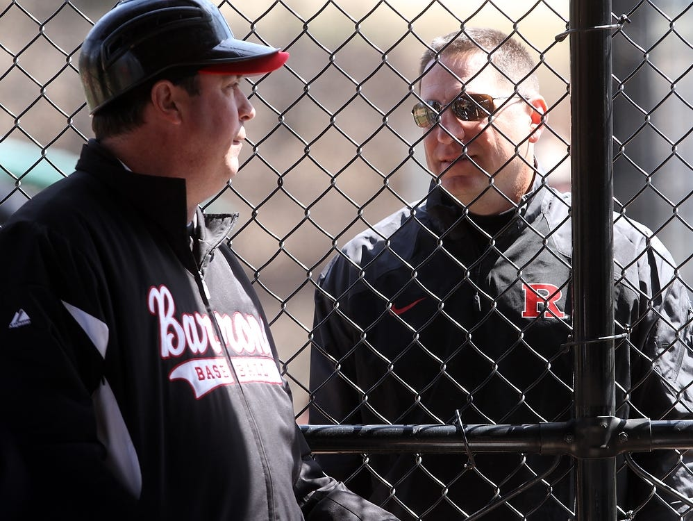 Rutgers University baseball coach Joe Litterio, right, speaks to Woodbridge coach Lou Urbano during the Barrons' game against JFK, Monday, April 6, 2015, in Woodbridge, NJ.