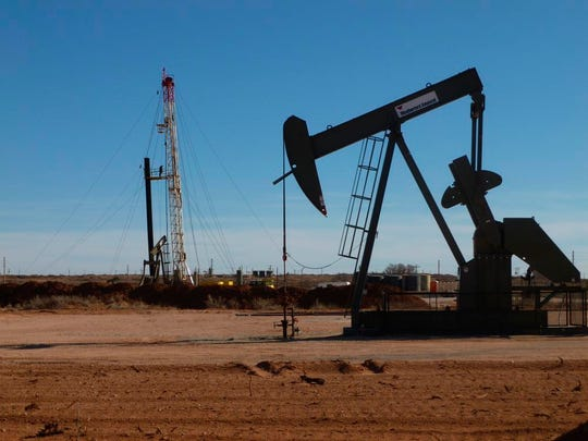 A drilling rig operates near a pump jack in Eddy County.