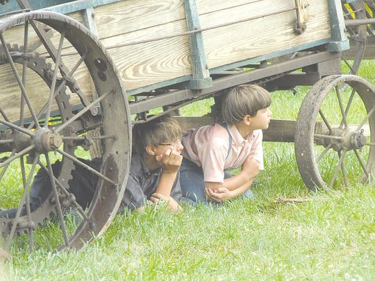 Two Amish boys escape from the rain during the miniature pony pulls by observing from under a wagon.