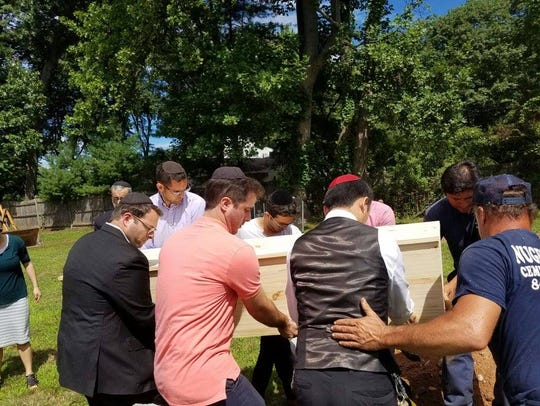 Mourners carry the casket at the funeral service for