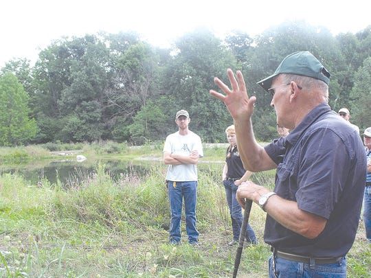 Gary Van Patten points out highlights of the restored pond on his 90-acre plot. The rocks are now being appreciated by turtles instead of residing in fields.