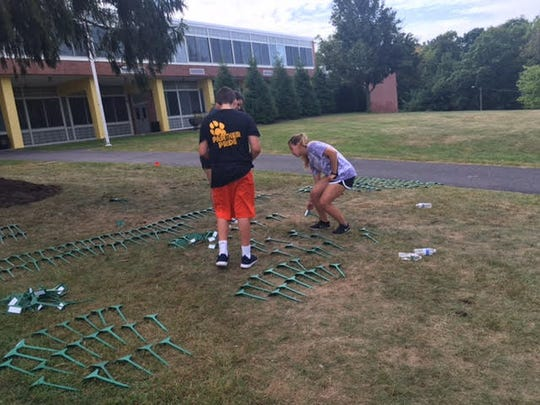 Caroline Fielding, right, sophomore, Chamberlain Ricco, left, freshman, and Elissa Johnson, in the back, junior, help put the names in the flags for the Cedar Grove Waves 9/11 memorial Sept. 9, 2016, at Cedar Grove High School.