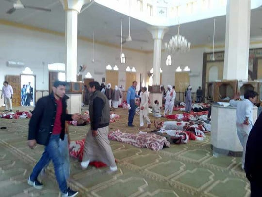 People sit next to bodies of worshippers killed in