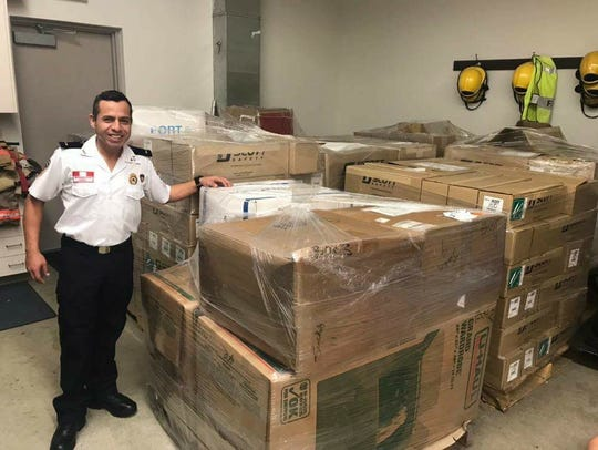 Lt. Juan Carlo Pacheco of Salamanca 127 in Lima, Peru, standing by some of the pallets of equipment to be donated to his fire station.