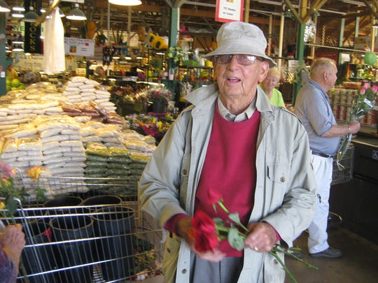"Jerald Horrocks, the founder of Horrocks Farm Market, greets customers with roses in Delta Township store in 2011. He died in 2014 at age 95. ""There wasn't really any situation that he couldn't handle,"" said granddaughter Autumn Horrocks."
