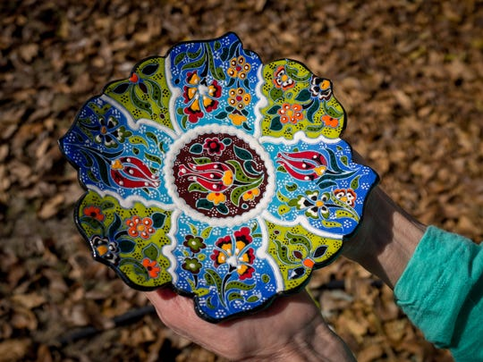 MariaElena (Ellen) Chavez holds up a contemporary decorative ceramic plate done in the Balkan style purchased during her Albania trip.