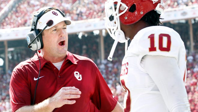 Oklahoma Sooners head coach Bob Stoops talks to defensive back Quentin Hayes (10) after a play against the Texas Longhorns during the Red River Rivalry at Cotton Bowl Stadium.