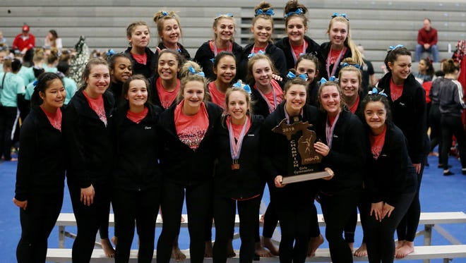 Livonia Blue celebrates after winning the MHSAA gymnastics regional held at Plymouth High School.