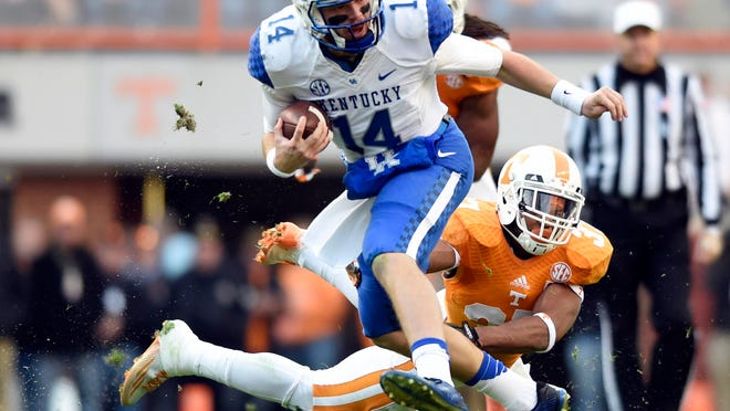 Tennessee's Brian Randolph makes the play on Kentucky quarterback Patrick Towles, who left after the first series Saturday with an ankle sprain but returned before halftime; he wore a protective boot on his left foot following the loss.