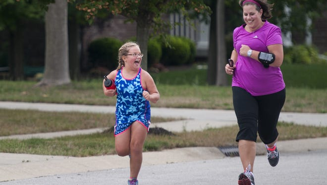 Susie McKenna and her daughter Hannah, 8, race back home during the final stretch of their half hour jog around their neighborhood in Zionsville, Ind., on Wednesday, Aug. 7, 2013.