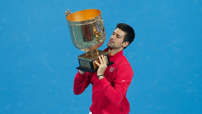 Novak Djokovic of Serbia poses with his trophy after defeating Rafael Nadal to win the China Open.