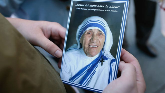 A tourist holds an image of Mother Teresa.