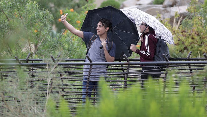 University of Texas at El Paso students Oscar Torres, left, and Javier Fraire take a photo at Centennial Plaza on campus Tuesday.