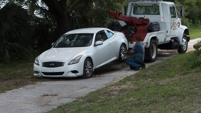 A Freeman Brothers Body Shop tow truck operator prepares to remove a vehicle from the Navy Point area Thursday, Aug. 10, 2017. The white car reportedly crashed into the water off Syrcle Drive in Navy Point.