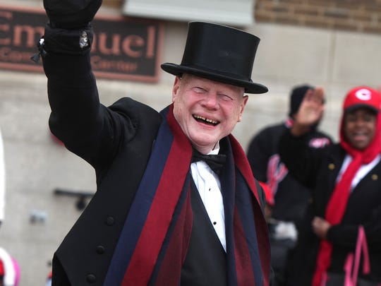 Jim Tarbell waves as he passes spectators in the  Findlay Market Opening Day Parade.