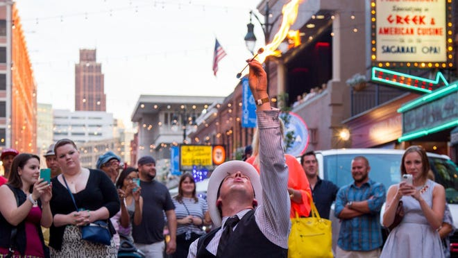 A fire eater entertains the crowd at a soft opening of the Greektown at Sundown weekend event series. The program runs through Labor Day.