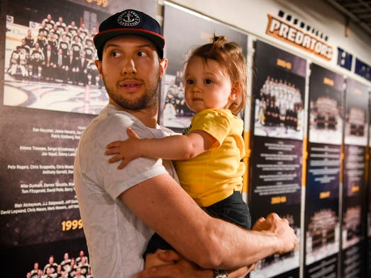 Nick Bonino holds his daughter Maisey as he looks back