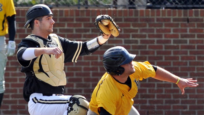 Vanderbilt catcher Chris Harvey tags out Long Beach State's Ino Patron at home plate.