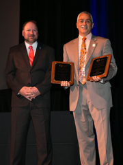 NJASBO School Business Administrator of the Year Derek J. Jess, right, is congratulated on stage at the annual conference by NJASBO President Louis Pepe.