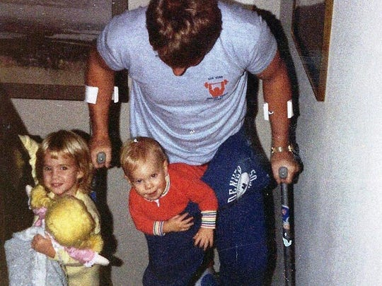 Despite his difficulty climbing the stairs in his home following a 1984 surgery, Rob Lytle helps his children, Erin, left, and Kelly, up the stairs.