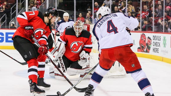 Columbus Blue Jackets defenseman Scott Harrington (4) battles with New Jersey Devils center Pavel Zacha (37) for a rebound during the first period at Prudential Center