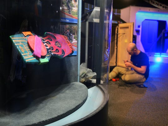 "Gavin Kinder, a technology designer with Stage Nine Exhibitions, works near a display of hoverboards from ""Back to the Future"" movies, part of the new installation, ""Interactive! The Exhibition"" at the Ronald Reagan Presidential Library & Museum in Simi Valley on Thursday. The exhibit opens to the public on Saturday."