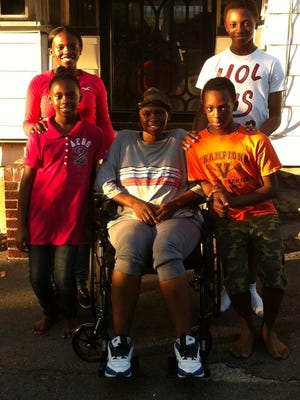 Mary Moore, center, is surrounded by her four of her five children. From bottom left, Deyonce, Xoviera, Dwayne and Khalique.